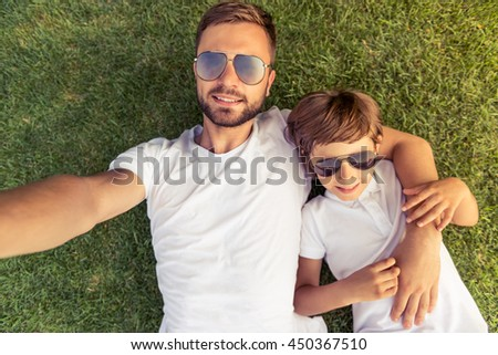 Top view of cute little boy and his handsome young dad in white T-shirts and sun glasses smiling while on the grass - stock photo