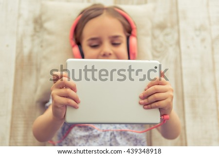 Top view of cute little girl in headphones listening to music using a tablet and smiling while lying on wooden floor - stock photo