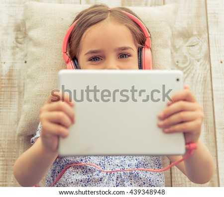 Top view of cute little girl in headphones listening to music using a tablet, looking at camera and smiling while lying on wooden floor