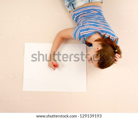 Top view of cute young woman looking up while lying on floor and drawing.