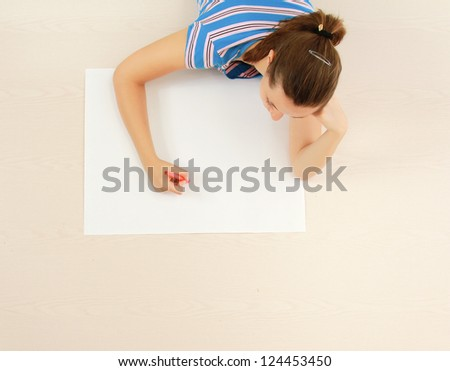 Top view of cute young woman thinking with a pen in her mouth while lying on floor and drawing.