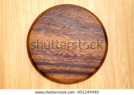 Top view of dark brown round wooden chopping block on light wood counter,Kitchenware. - stock photo