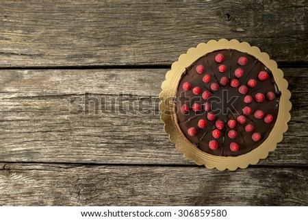Top view of delicious chocolate cake decorated with juicy fresh raspberries on old textured wooden desk with plenty of copy space on the left side. - stock photo
