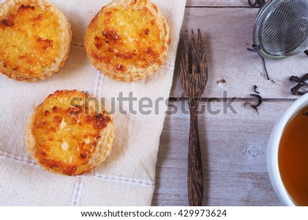 Top view of delicious coconut custard tarts on a napkin with tea cup and infuser. - stock photo