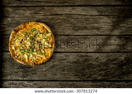 Top view of delicious freshly baked vegetarian pizza topped with eggplant, green  peppers and anchovies, lying to the left side on old textured rustic wooden board with copyspace. - stock photo