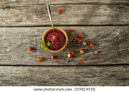 Top view of delicious freshly made fruit jam in a small bowl decorated with mint leaves with fresh strawberries scattered around on a textured rustic wooden planks.  - stock photo