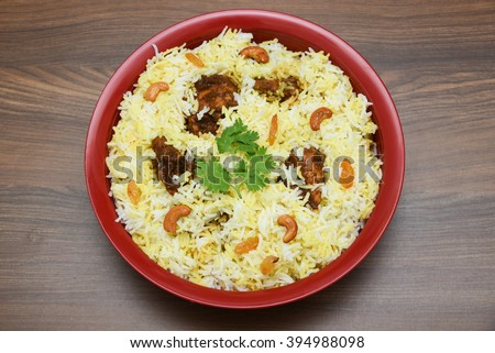 Top view of delicious North Indian food Hydrabadi chicken biriyani, Dum Biriyani, Chicken pulao seasoned corriander leaves. basmati rice, herbs, raitha.  Ramadan Kareem, Eid-Ul-Adha - stock photo