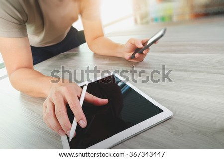 top view of Designer hand working with digital tablet computer and smart phone on wooden desk as responsive web design concept