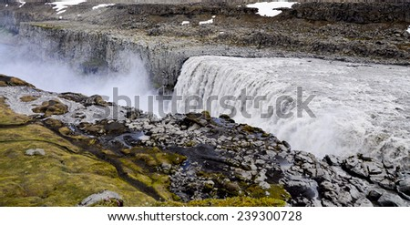 Top view of Dettifoss waterfall in Iceland with some tourists walking on the west side - stock photo