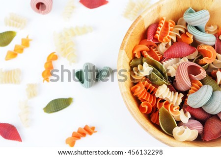 Top view of different type of colorful pasta in a wooden bowl on white background. Selective focus. - stock photo
