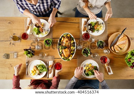 Top view of dining table with salad and roasted chicken with potatoes. High angle view of happy young friends having lunch at home. Men and women eating lunch together.  - stock photo
