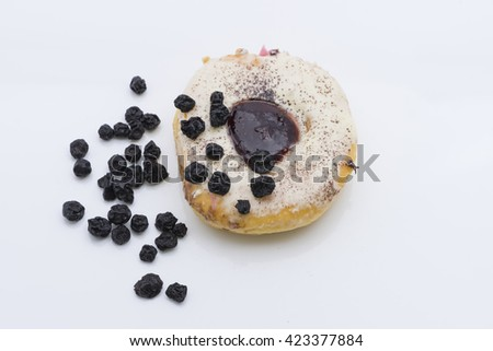 Top view of doughnut. The ring shaped donut, fried and glazed with icing, topped with cinnamon powder sprinkles and blueberry jam. Garnished with some dried blueberries. Isolated on white background. - stock photo