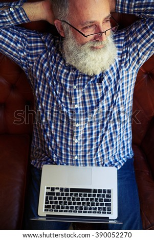 top view of dreaming senior man with laptop on sofa - stock photo