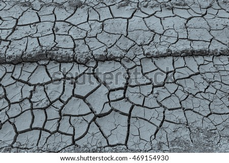 Top view of dried ground covered with cracks . Natural dry soil texture, brown drought theme in rural arid area. Background for design. Concept image of global warming. Black and white.