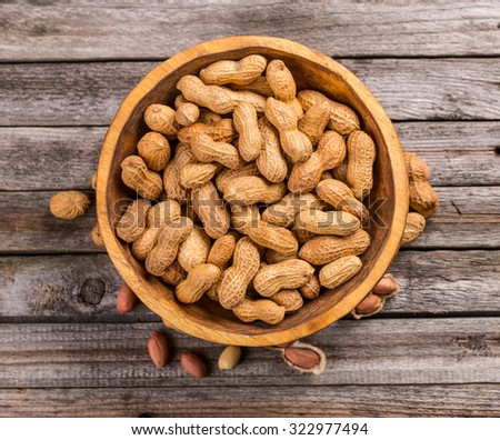 Top view of dried peanuts in wooden bowl