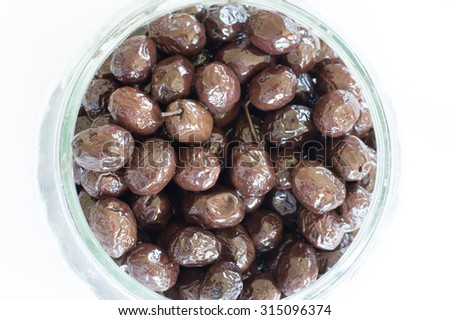 Top view of edible organic black olives in a glass container