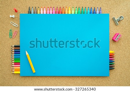 Top view of education and art supplies on cork table with empty space color paper - stock photo