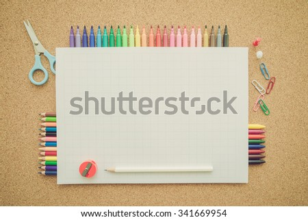 Top view of education and art supplies on cork table with empty space tabulation paper - Retro filter effect - stock photo
