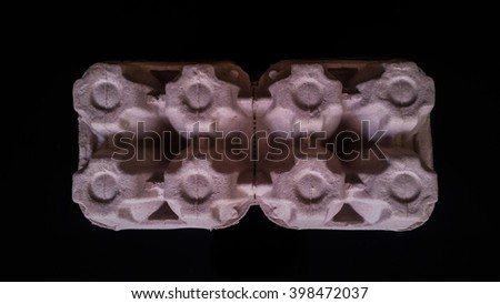 Top view of egg box on a black background