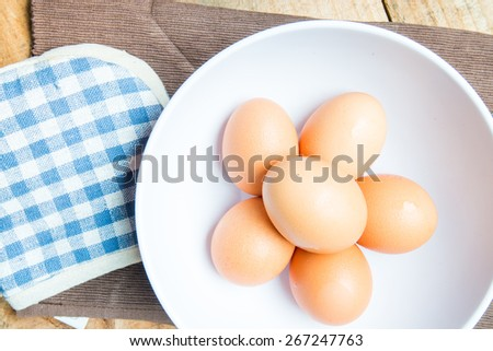 top view of eggs in bowl and cloth and glove