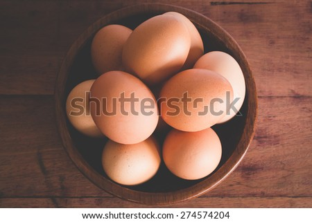 top view of eggs in bowl wooden on wood table - stock photo