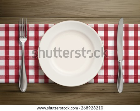 top view of empty plate with spoon and knife placed on wooden table - stock photo