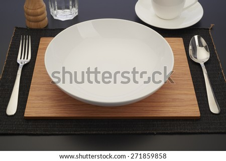 top view of empty plate with spoon and knife placed on wooden table