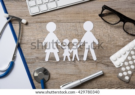 Top view of family paper chain on a doctor desk. Medical worktable with keyboard, blue stethoscope, pills and eyeglasses. Family healthcare, medicine and insurance concept. - stock photo