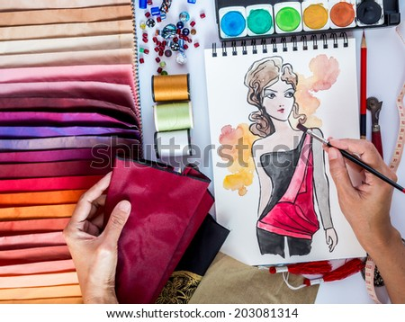 Top view of fashion designer working with material sample and hand-drawn illustration - stock photo