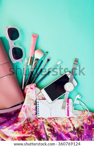 Top view of female fashion accessories for woman. Stylish sunglasses, pink bag, silver watch, lipstick, smart phone, make up brushes,notebook. Overhead of essentials for modern young person.   - stock photo
