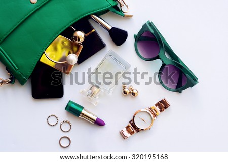 Top view of female fashion accessories . Green handbag with  sunglasses,  gold watch , lipstick , perfume , rings , smart phone - stock photo
