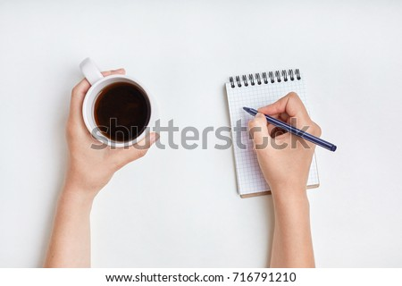 Top view of female hand writes in spiral notebook, takes notes with cup of tea. Woman writes in her diary. Beautiful female's hand holds pen above notebook paper with mug of coffee