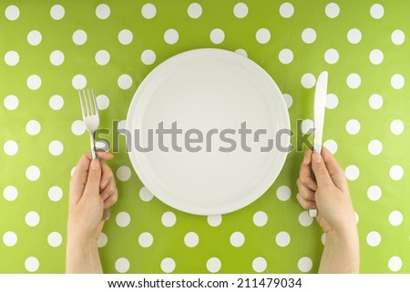 Top view of Female hands at dinner table holding fork and a knife above empty flat white plate, dieting concept. - stock photo