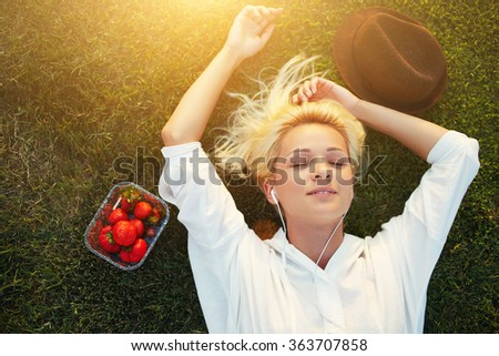 Top view of female student listening to music with headphones while lying on lawn after University lectures, young charming woman with closed eyes enjoying sunshine during recreation time in the park - stock photo