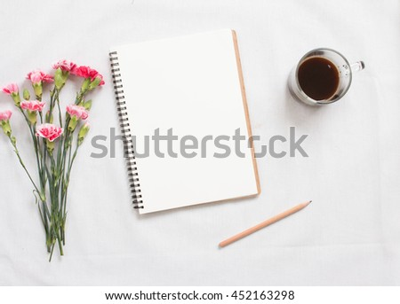 Top view of flowers and  blank notebook on white fabric workspace background. - stock photo