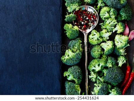 Top view of Food background with fresh green broccoli and spices. Slate and wood background with copyspace.  - stock photo