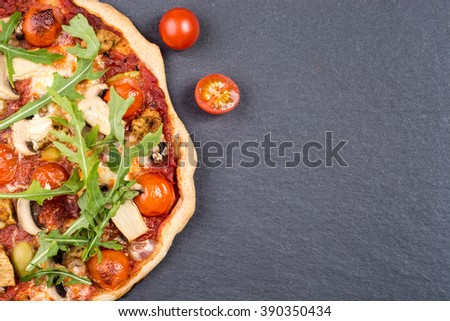 Top view of fresh baked pizza with mushrooms and fresh rocket herbs - stock photo