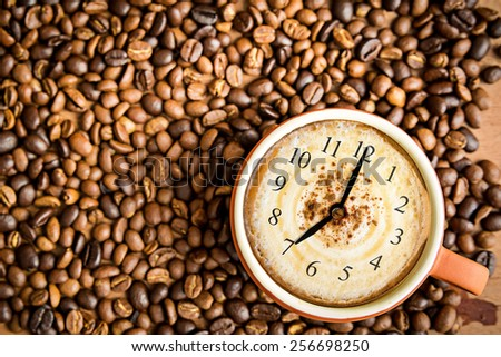 top view of fresh cappuccino with clock sign and coffee beans  - stock photo