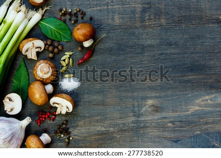 Top view of fresh mushrooms and ingredients on dark wooden background. Vegetarian food, health or cooking concept. - stock photo