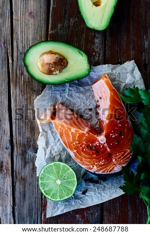 Top view of fresh salmon steak, avocado, lime and parsley on rustic wooden background - healthy food, diet or cooking concept.  - stock photo