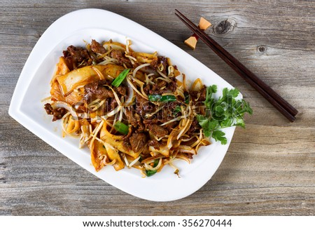 Top view of freshly cooked spicy beef, bean sprouts, onion, tofu with parsley as garnish and chopsticks in holder on rustic wood.  - stock photo
