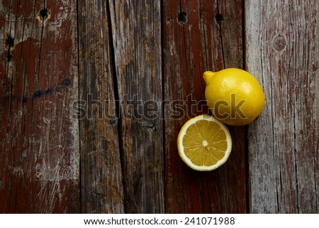 Top view of freshly cut half and whole lemons on rustic wooden background. - stock photo