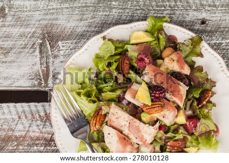 Top view of freshly harvested lettuce, grilled chicken, avocado, raspberry, pecan salad on an old weathered barn wood table background - stock photo