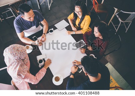 top view of friends at cafe talking about something on white paper - stock photo