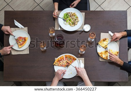 Top view of friends eating pizza and salad on a woooden table in a restaurant.