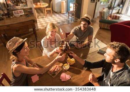 Top view of friends having a drink and playing poker on a sunny evening. They are sitting at a wooden table in a cozy house with beers and tortilla chips. They are wearing casual clothes and hats. - stock photo