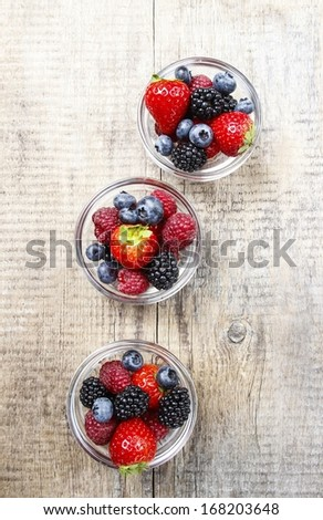 Top view of fruit salad in small transparent bowls on wooden table - stock photo
