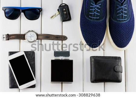 Top view of gentlemanly set: blue shoes, car keys, sunglasses, watch, document, smartphone, perfume and wallet on white wooden background - stock photo