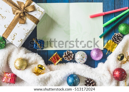 Top view of Gift box with Christmas decoration and card on wooden table background.