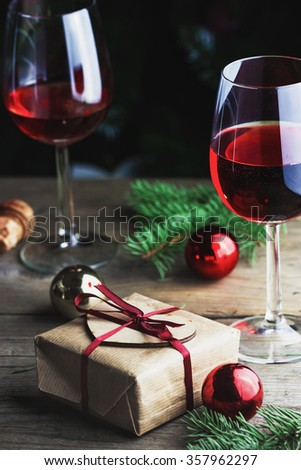 Top view of gift box with glasses of red wine and color Christmax balls with fir-tree branches on wooden background